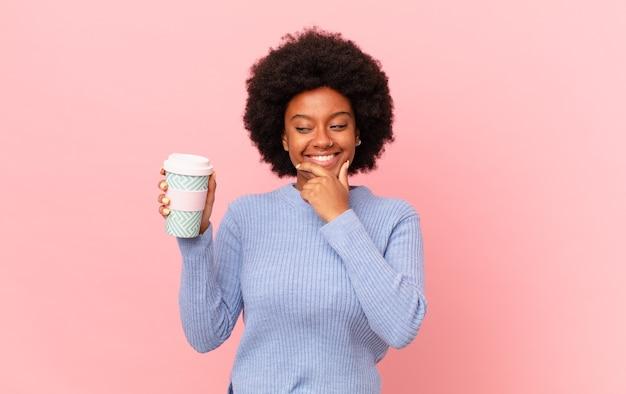 Mulher afro sorrindo com uma expressão feliz e confiante com a mão no queixo, pensando e olhando para o lado. conceito de café