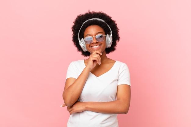 Mulher afro sorrindo com uma expressão feliz e confiante com a mão no queixo, pensando e olhando para o lado