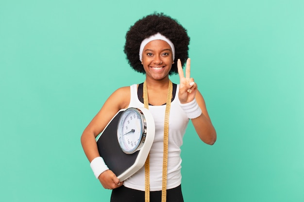Mulher afro sorrindo e parecendo amigável, mostrando o número dois ou o segundo com a mão para a frente, conceito de dieta em contagem regressiva