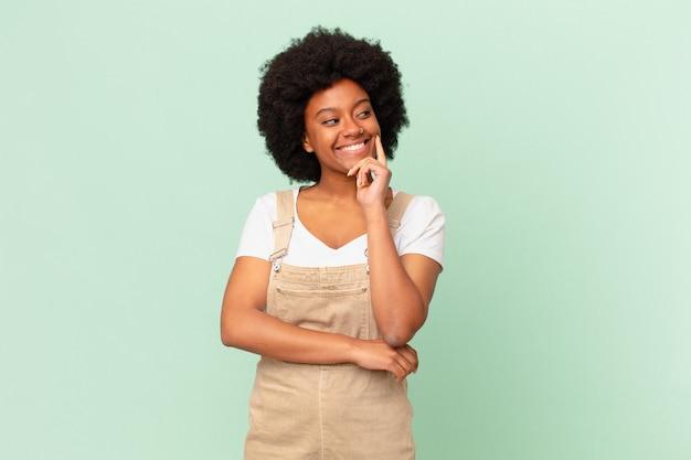 Mulher afro sorrindo feliz e sonhando acordada ou duvidando, olhando para o lado do conceito do chef