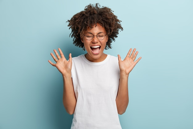 Mulher afro superemotiva ri alto, ouve uma piada ou história engraçada, levanta as palmas das mãos com satisfação