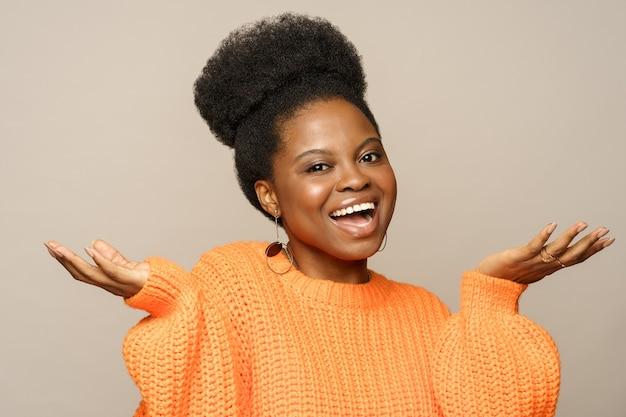 Mulher afro surpresa emocionalmente levantando as mãos em sinal de espanto, encolhendo os ombros, sorrindo em estúdio.
