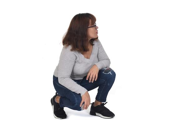 Mulher agachada olhando para o fundo branco