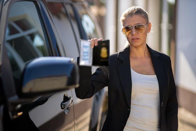 Mulher agente especial da inteligência federal de terno preto e grande carro de polícia