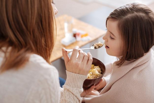 Mulher agradável e adorável segurando uma colher e dando café da manhã para sua filhinha