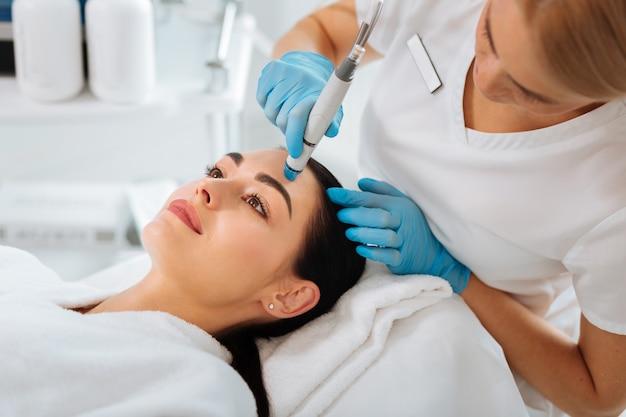 Mulher agradável e agradável deitada sobre o médico durante um procedimento de beleza