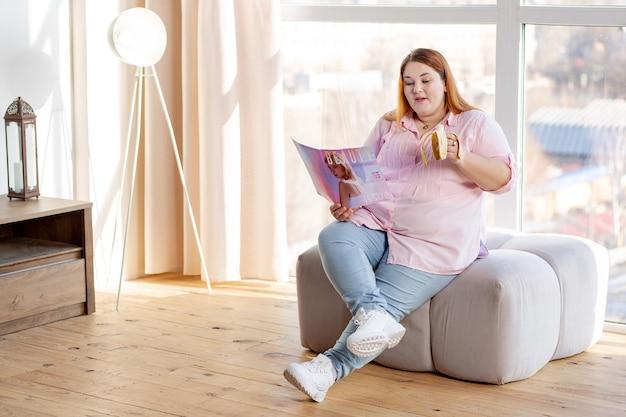 Mulher agradável e agradável lendo uma revista enquanto segue as tendências de beleza modernas