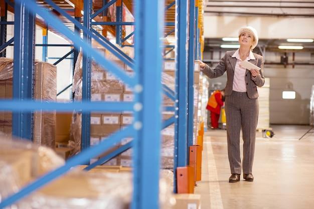 Mulher agradável e agradável olhando para as prateleiras de armazenamento enquanto trabalhava como gerente de entrega no armazém