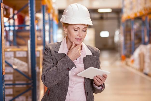 Mulher agradável e agradável olhando para seu tablet enquanto trabalhava como gerente de depósito