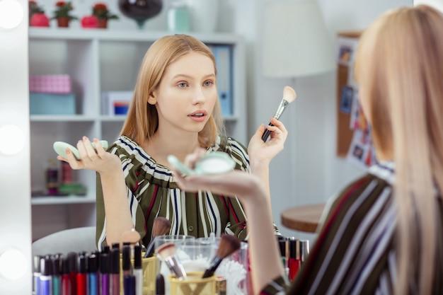 Mulher agradável e agradável se maquiando enquanto se prepara para sair