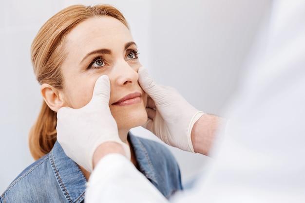 Mulher agradável e atraente sentada em frente ao médico, olhando para ele durante o exame médico