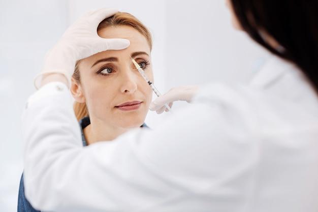 Mulher agradável e séria visitando um cosmetologista e tomando injeções de botox enquanto deseja permanecer jovem