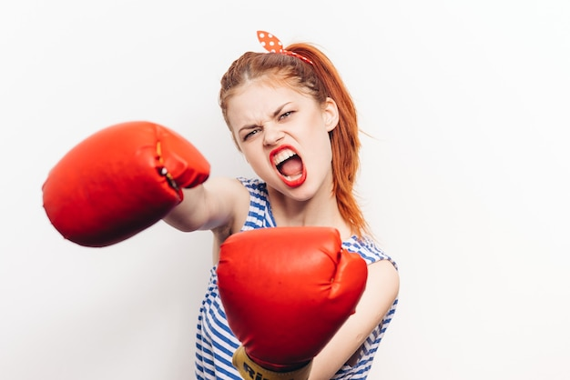 Mulher agressiva com luvas vermelhas de luta livre em um fundo claro, boca bem aberta, vista cortada
