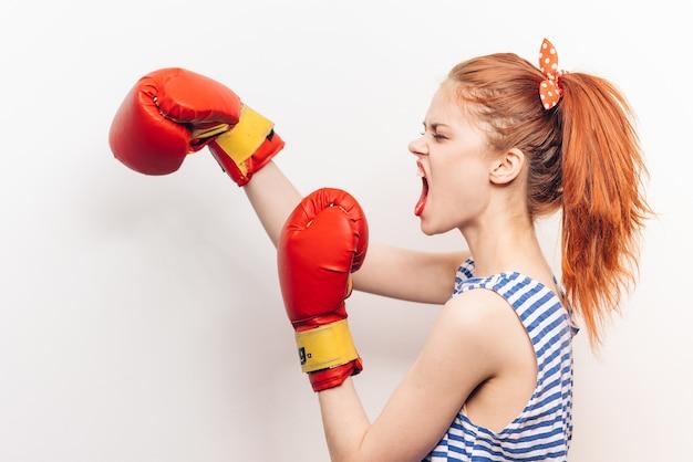 Mulher agressiva fazendo boxe esportivo modelo de penteado com camiseta listrada