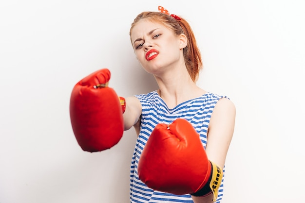 Mulher agressiva no boxe em um fundo claro com uma camiseta listrada e luvas vermelhas cortou a vista