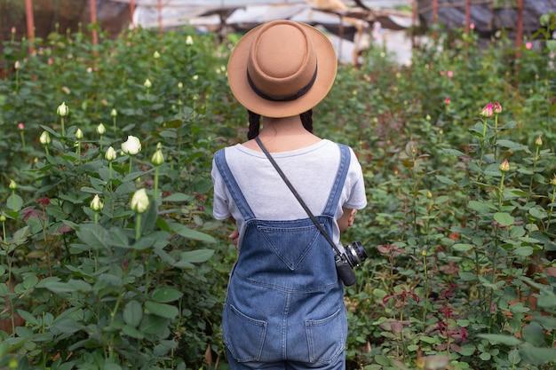 Mulher agrícola que guarda uma tabuleta no jardim de rosas.