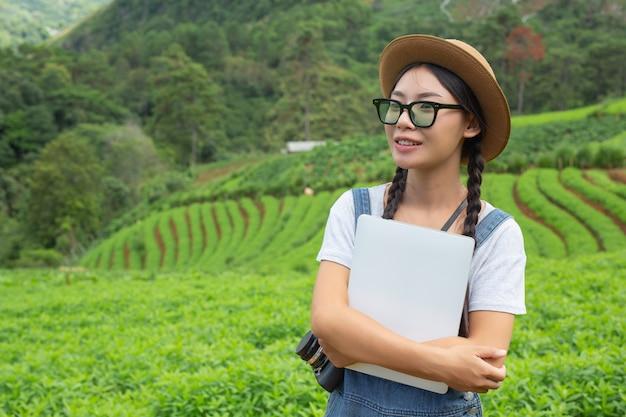 Mulher agrícola que inspeciona a planta com comprimidos de criação - um conceito moderno