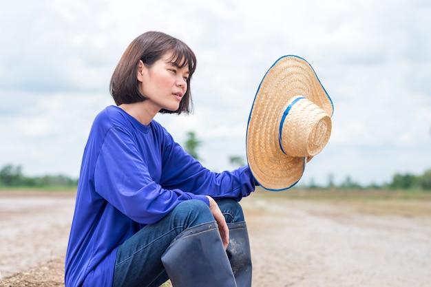 Mulher agricultora asiática sentada à espera de água para plantar arroz na fazenda na estação das chuvas