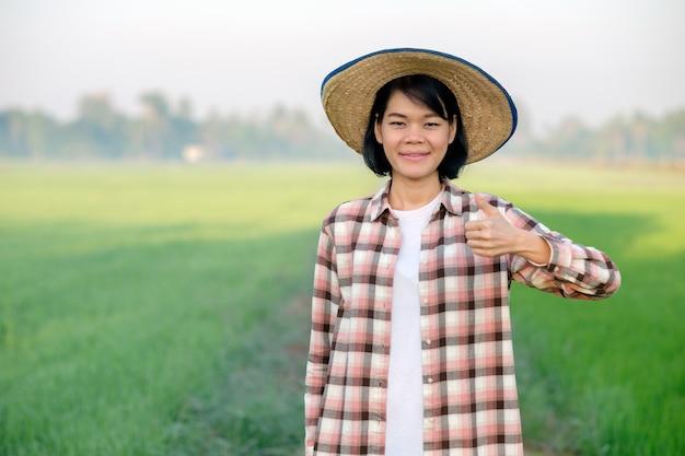 Mulher agricultora asiática sorri com um chapéu e posa com o polegar para cima em uma fazenda de arroz verde