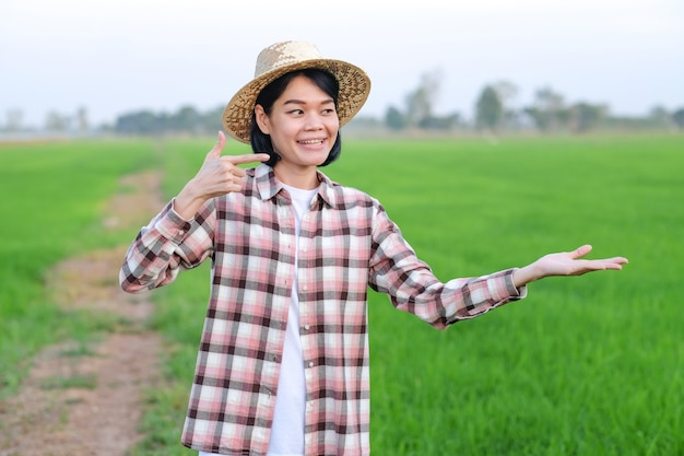 Mulher agricultora asiática sorrindo e olhando pose erguer coisas em uma fazenda de arroz verde