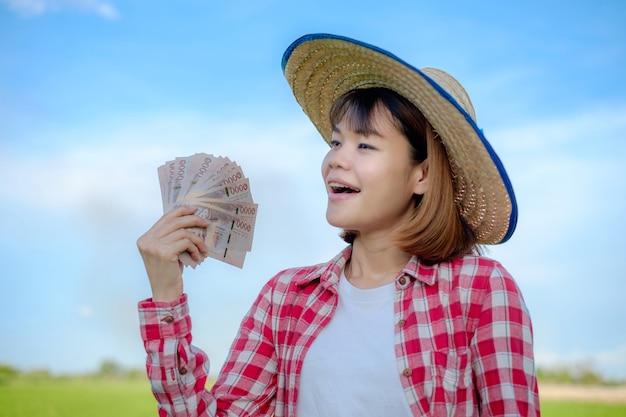 Mulher agricultora asiática sorrindo e segurando o dinheiro da nota na fazenda de arroz verde