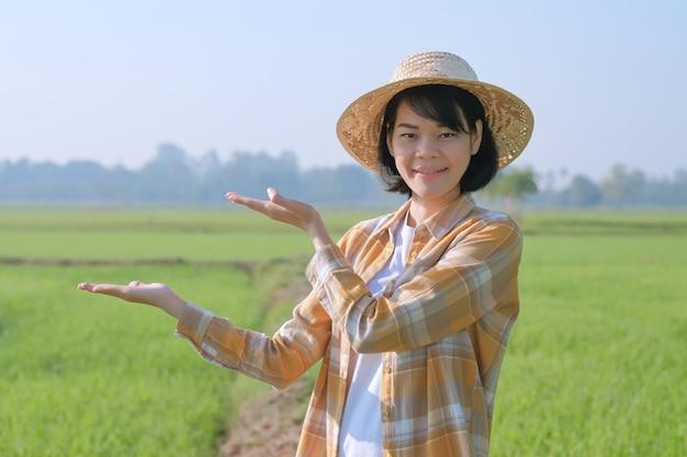 Mulher agricultora asiática usa camisa amarela levantada com as mãos para a apresentação de produtos na fazenda de arroz verde