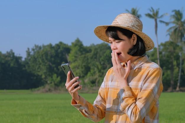 Mulher agricultora asiática usando smartphone com cara de surpresa uau na fazenda de arroz