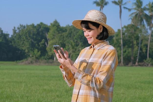 Mulher agricultora asiática usando smartphone e polegar para cima na fazenda verde