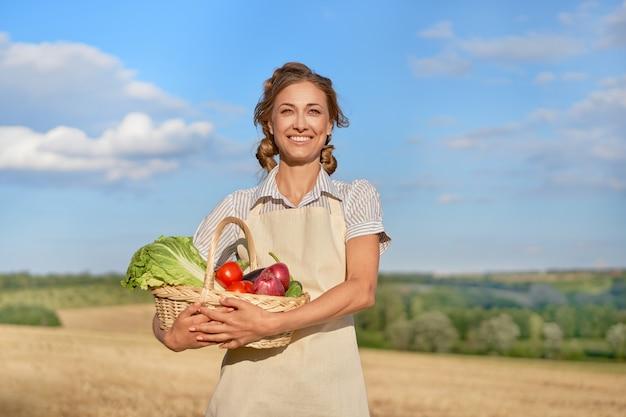 Mulher agricultora avental em pé terra arável sorrindo especialista em agrônomo feminino do agronegócio agrícola feliz positivo caucasiano trabalhador campo agrícola