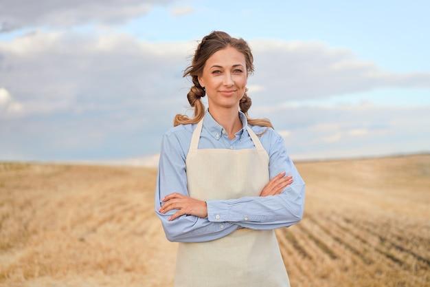 Mulher agricultora avental em pé terra arável sorrindo mulher agrônoma especialista em agronegócio agrícola feliz positivo caucasiano trabalhador campo agrícola