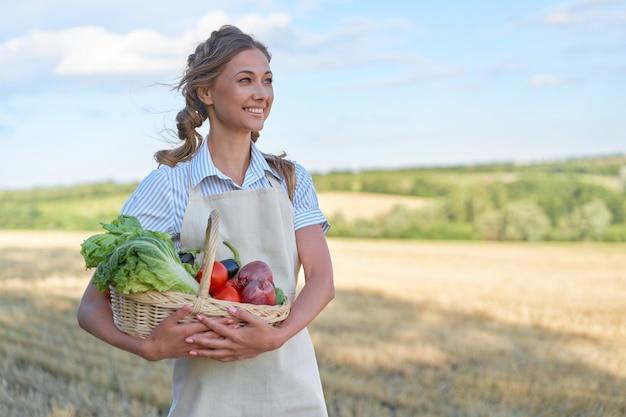 Mulher agricultora avental em pé terra cultivada sorrindo mulher agrônoma especialista em agronegócio agrícola