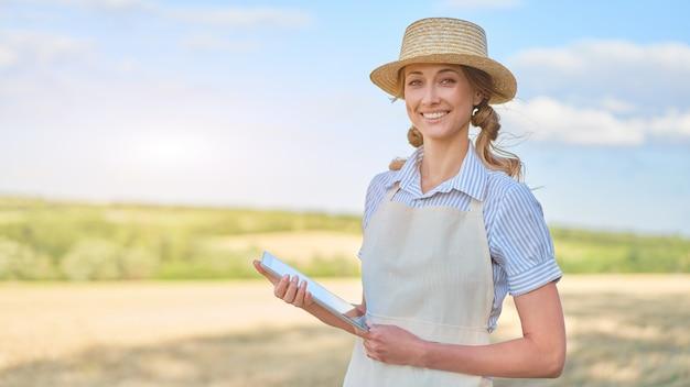 Mulher agricultora chapéu de palha agricultura inteligente em pé terra cultivada sorrindo usando tablet digital mulher especialista em agrônoma pesquisa monitoramento análise de dados agronegócio