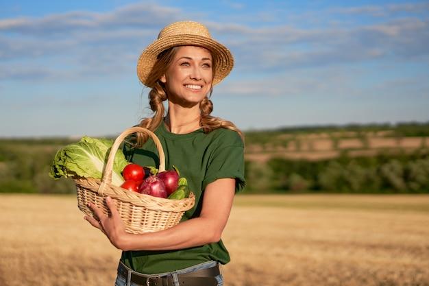 Mulher agricultora, chapéu de palha, avental em pé, fazenda, sorrindo