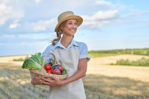 Mulher agricultora, chapéu de palha, avental, terra arável, sorrindo mulher agrônoma especialista em agronegócio agrícola