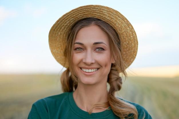 Mulher agricultora chapéu de palha em pé terra cultivada sorrindo especialista em agrônomo feminino do agronegócio agrícola feliz positivo caucasiano trabalhador campo agrícola