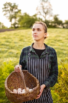 Mulher agricultora coletando ovos