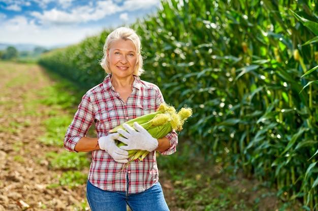 Mulher agricultora com uma colheita de milho.
