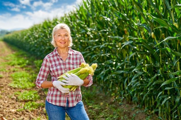Mulher agricultora com uma safra de milho.