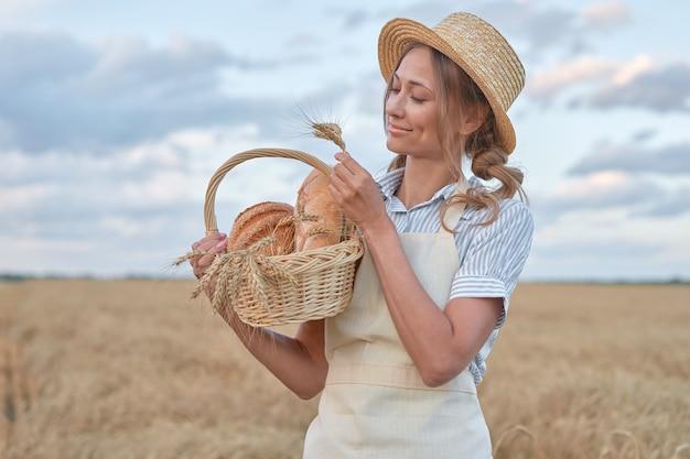 Mulher agricultora em pé campo agrícola de trigo mulher padeiro segurando uma cesta de vime produto de pão