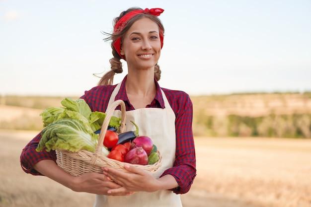 Mulher agricultora em pé, sorrindo, agrônomo feminino especialista em agronegócio agrícola. campo agrícola trabalhador feliz positivo caucasiano