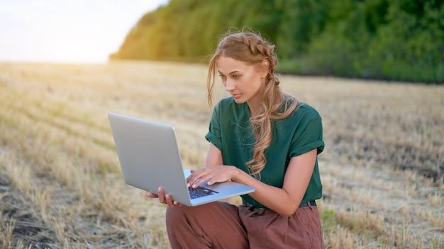 Mulher agricultora inteligente agricultura em pé terra arável sorrindo usando laptop mulher agrônoma especialista em pesquisa, monitoramento de análise de dados agronegócio