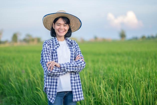 Mulher agricultora sorrindo e cruzando as mãos em uma fazenda de arroz verde