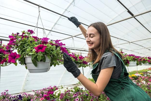 Mulher agricultora trabalhando em um centro de jardim e cuidar de suas flores diferentes. primavera