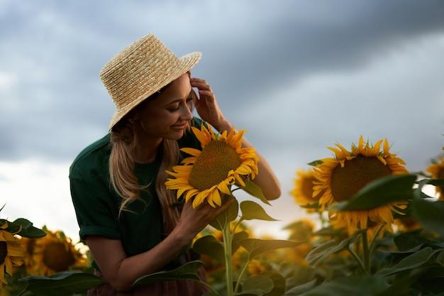 Mulher agrônoma em pé campo de girassol agrícola caucasiana mulher agricultora chapéu de palha
