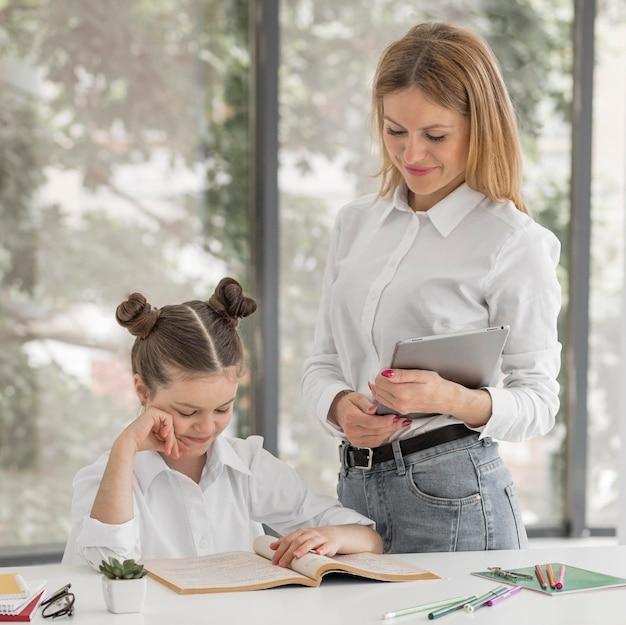 Mulher ajudando a filha com suas aulas