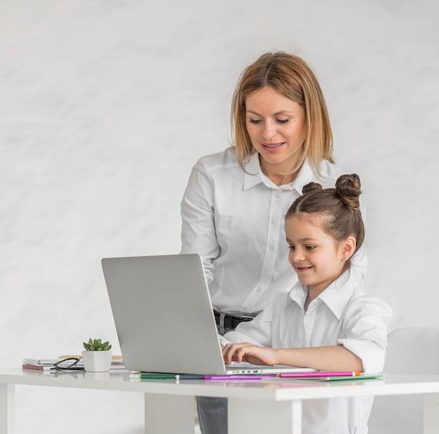 Mulher ajudando a filha durante uma aula on-line