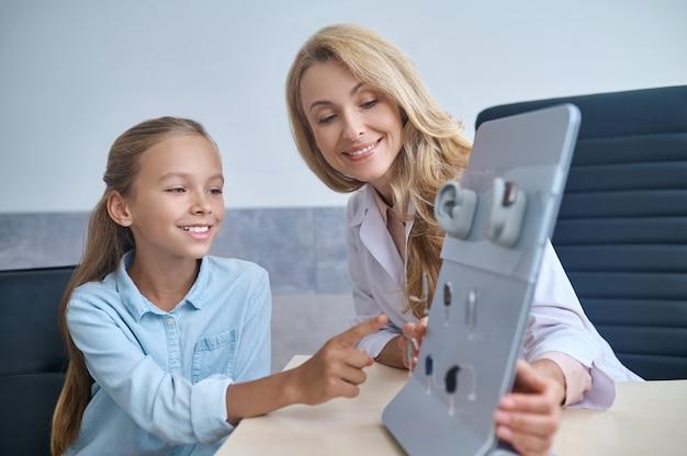 Mulher ajudando a garota a escolher aparelho auditivo.
