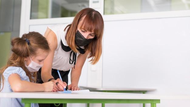 Mulher ajudando aluno durante a pandemia com espaço de cópia
