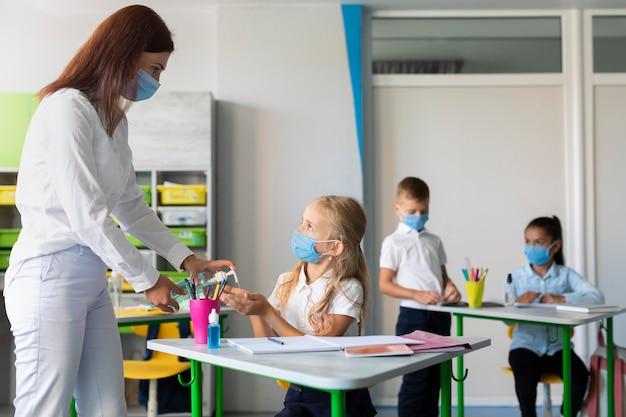 Mulher ajudando crianças a desinfetar as mãos