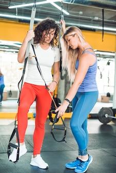 Mulher, ajudando, dela, amigo, enquanto, exercitar, com, aptidão, cinta, em, ginásio